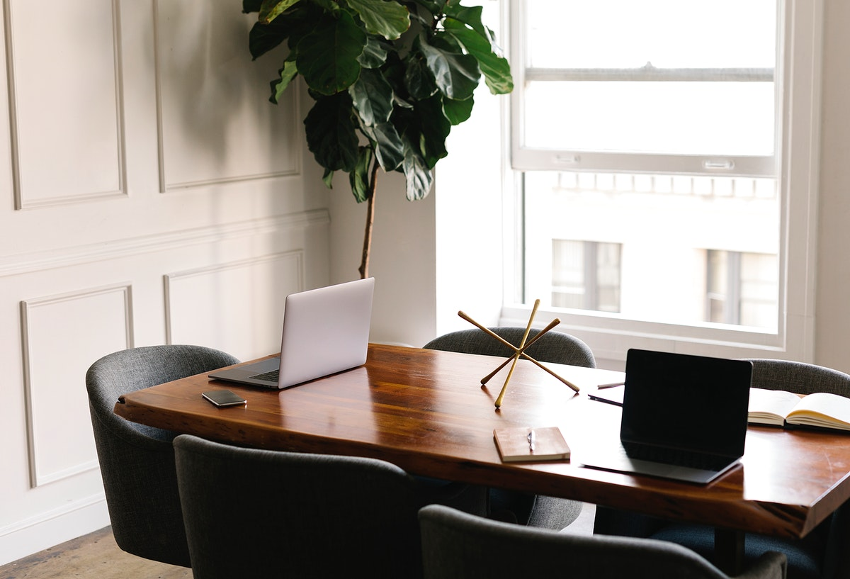 Laptop on a wooden table in a meeting room