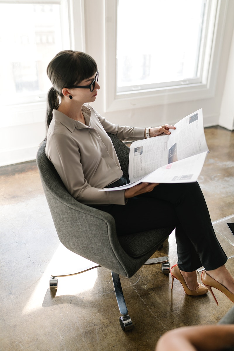 Young businesswoman reading a newspaper