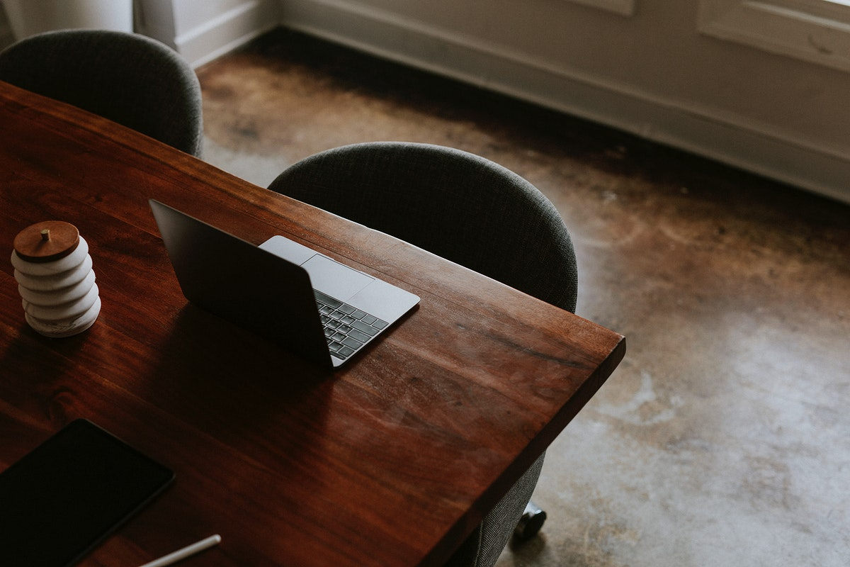 Digital tablet and a laptop on a wooden table in a meeting room