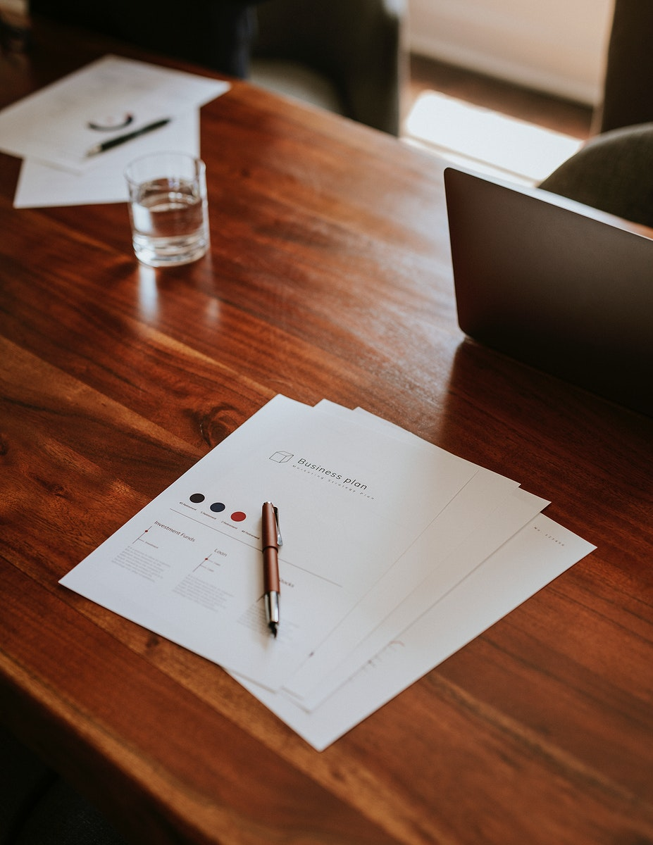 Signing documents in an office on a wooden desk