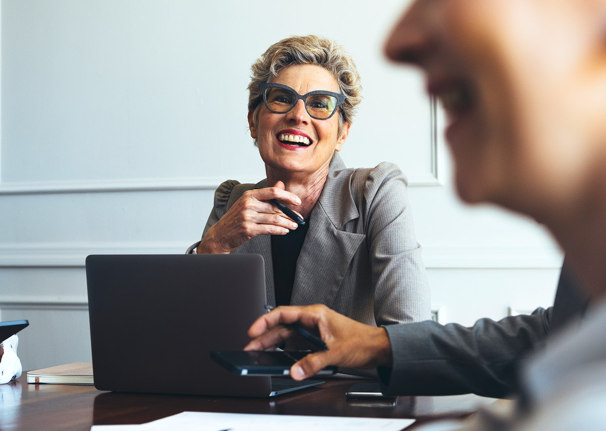 Cheerful short blond-haired businesswoman in a meeting