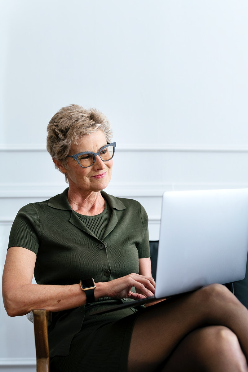 Cheerful short blond-haired businesswoman using a laptop