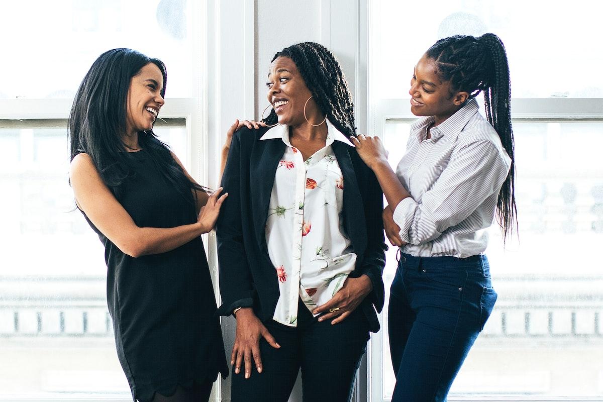 Happy black businesswomen standing by window