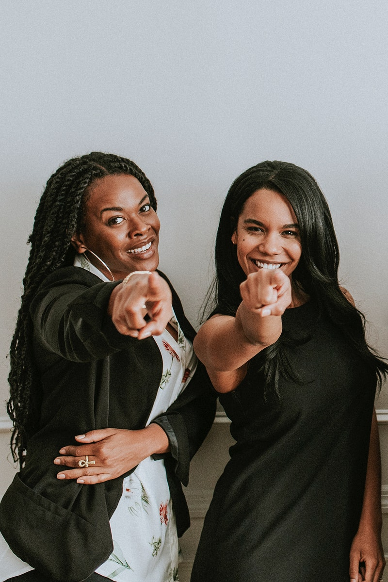 Two cheerful black women pointing at a camera