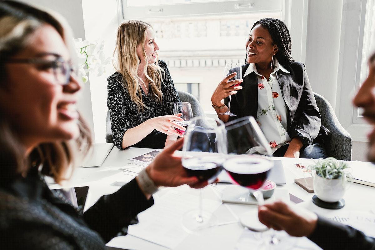 Diverse businesswomen drinking wine in the meeting room