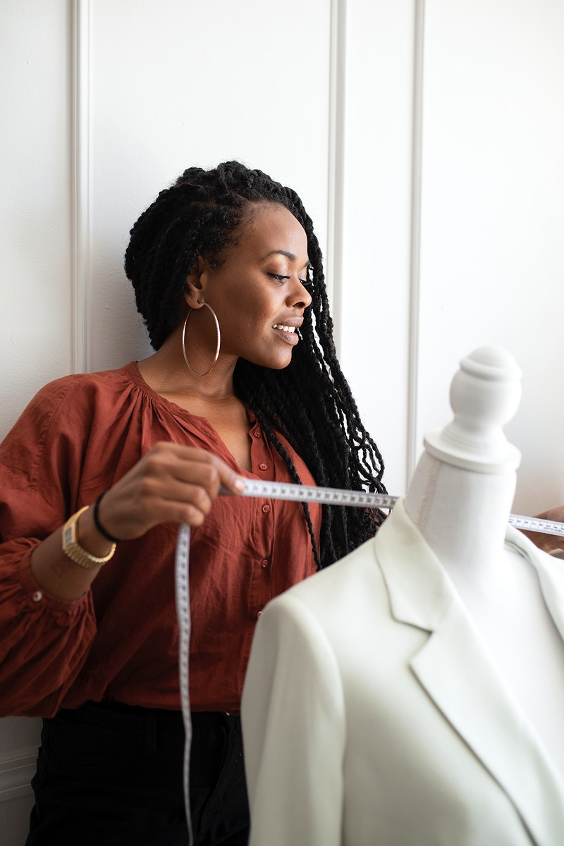 Black fashion designer measuring a white coat on a pinnable mannequin