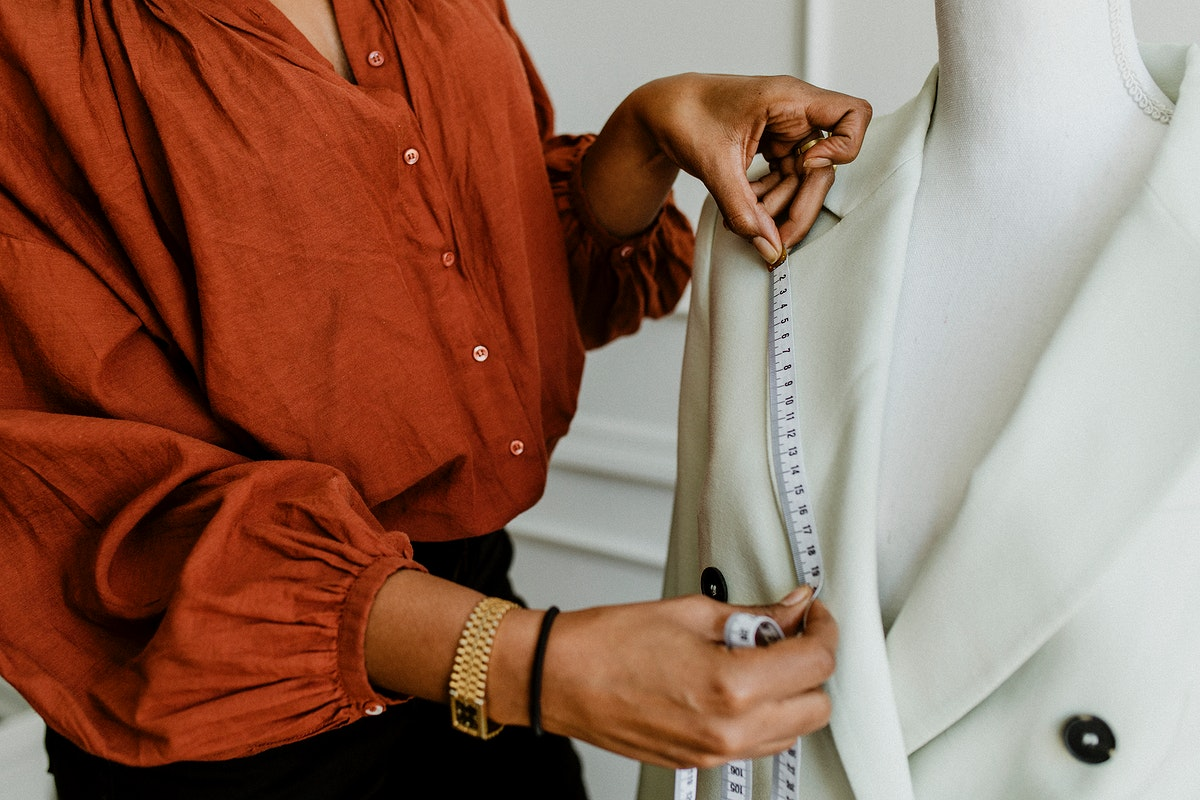 Fashion designer measuring a blazer on a pinnable mannequin