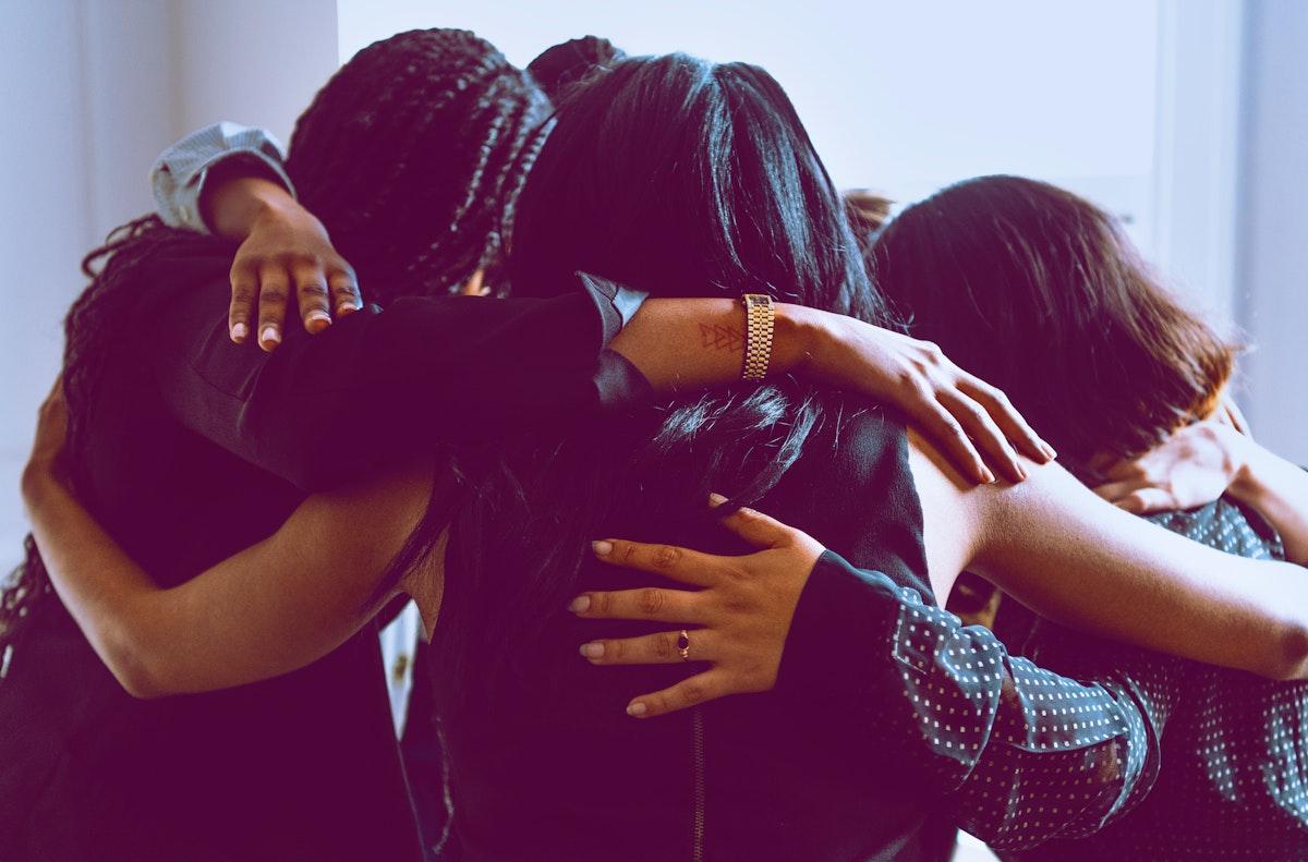 Happy diverse businesswomen huddling in the office