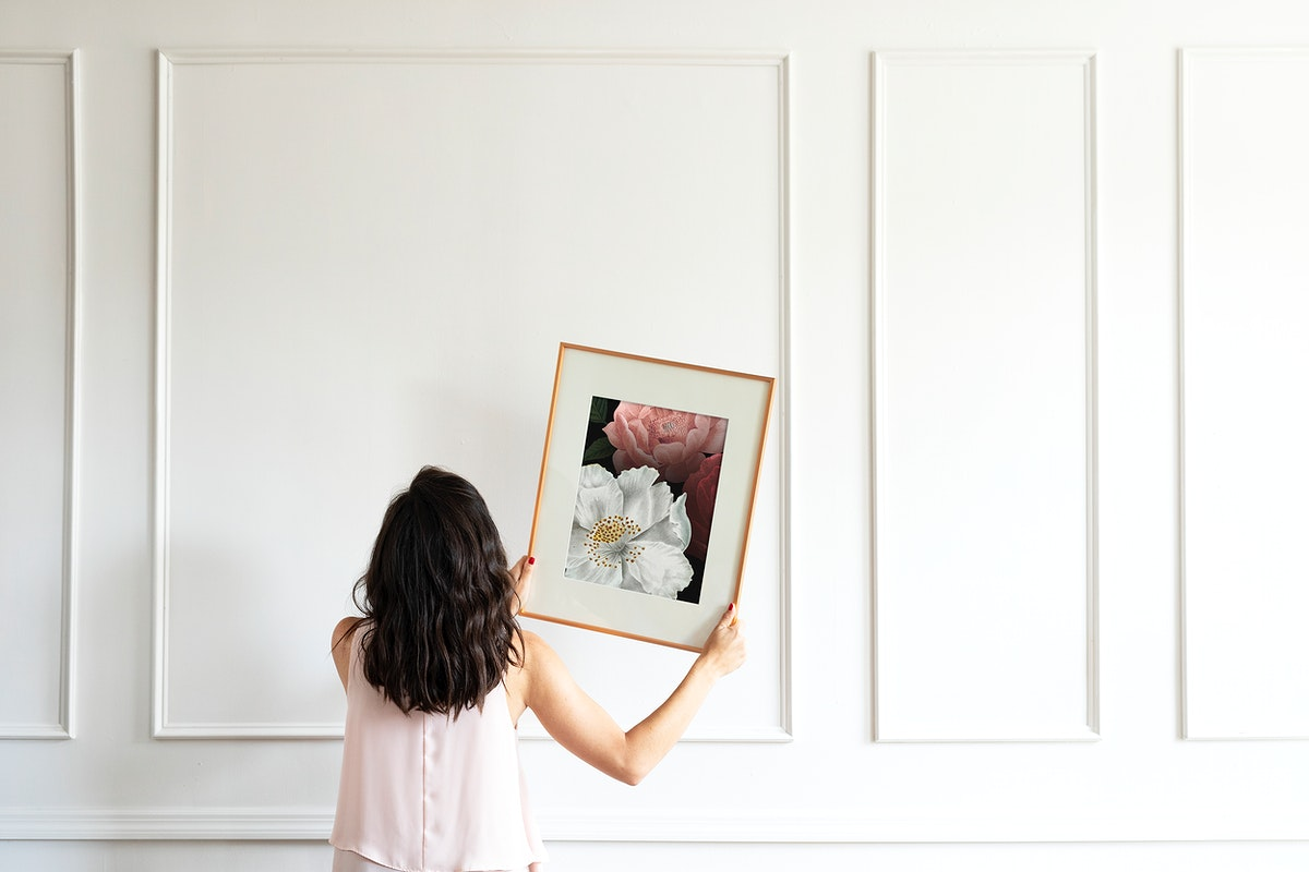 Curator hanging floral art frame mockup on the wall