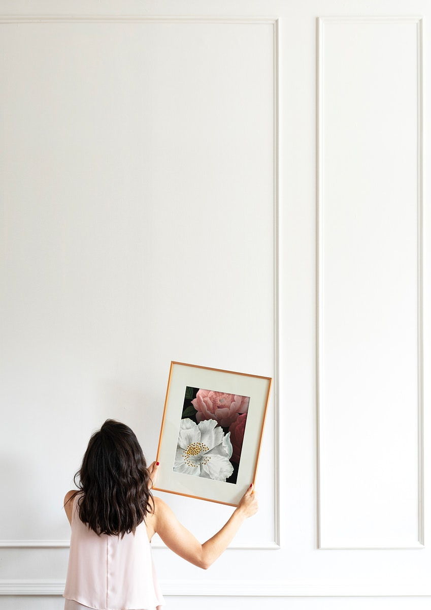 Curator hanging floral art frame on the wall