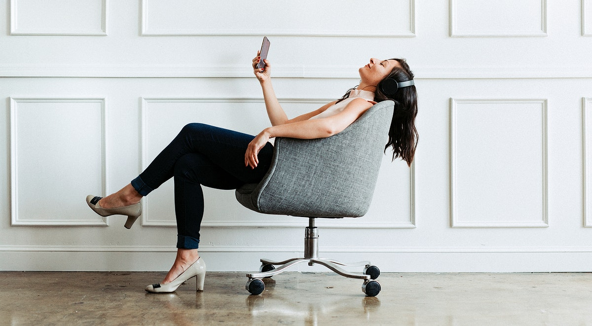 Female sitting on a chair listen to music