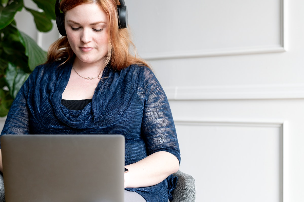 Businesswoman with headphone using a laptop