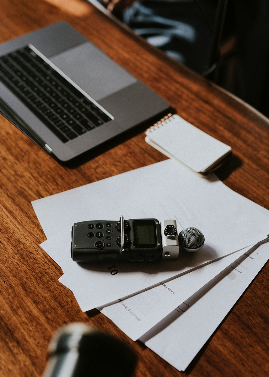 Journalist's  portable sound recorder on white papers