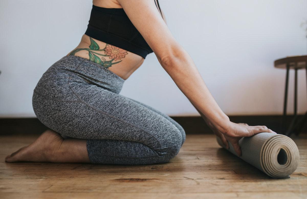 Sporty woman rolling a yoga mat