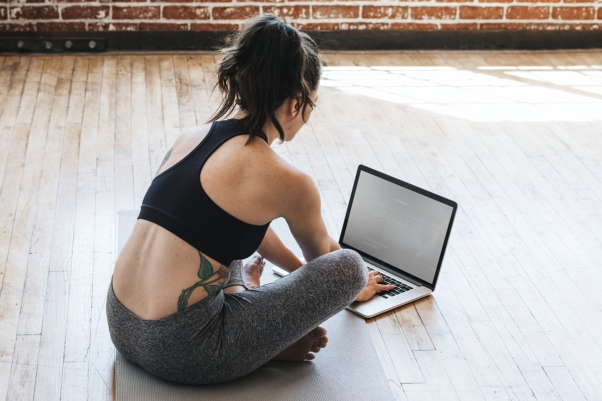 Active woman practicing yoga using a laptop