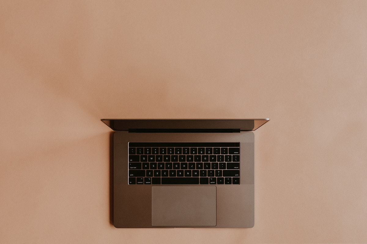 Laptop lying on a peach background