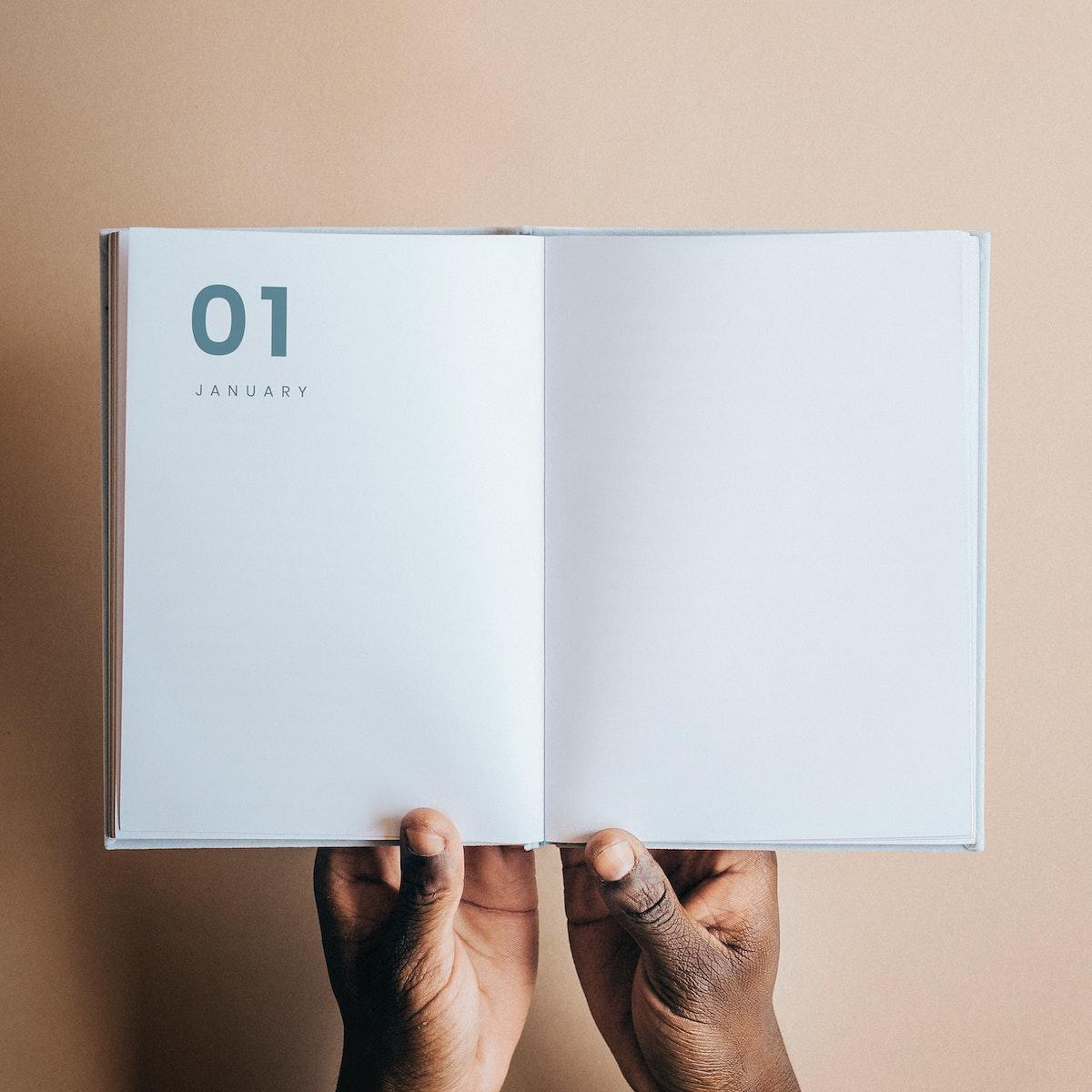 Black man holding a book planner mockup