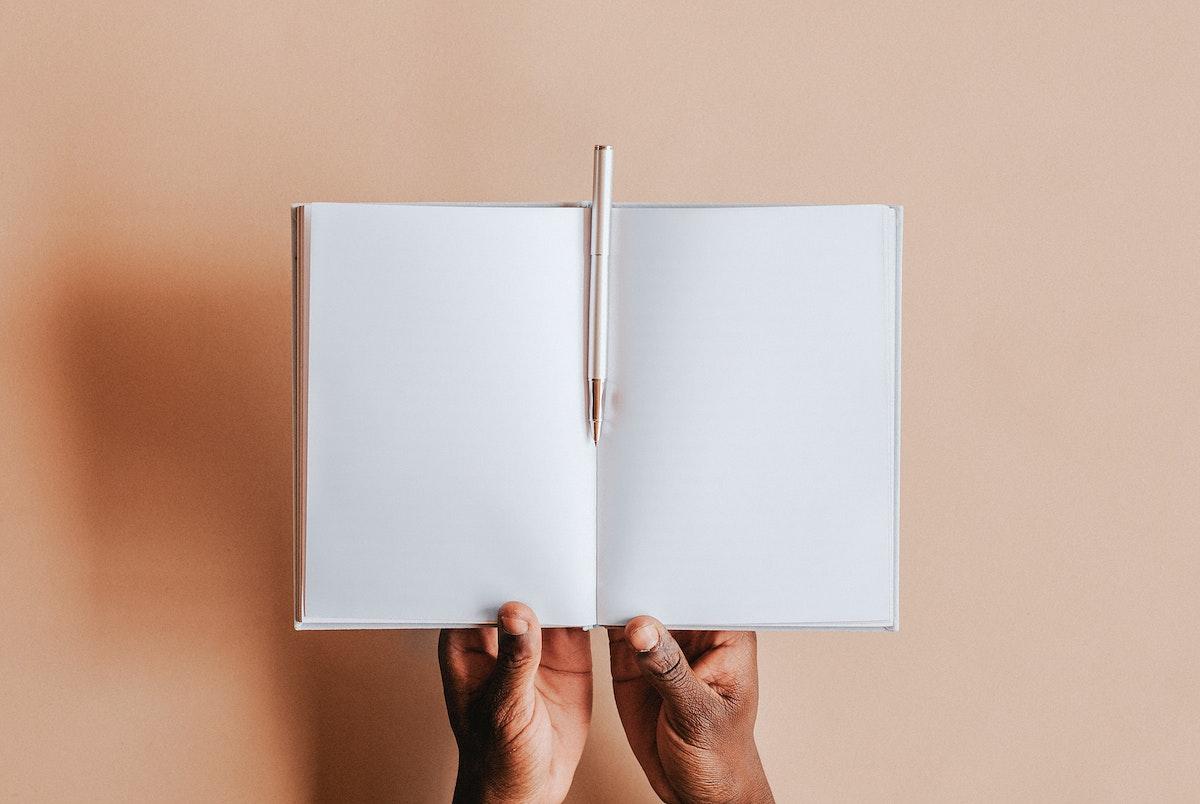 Black man holding an empty notebook mockup