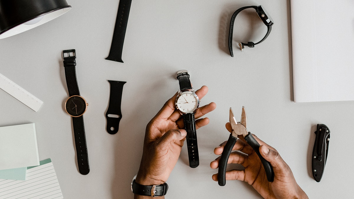 Horologist fixing a watch with pliers