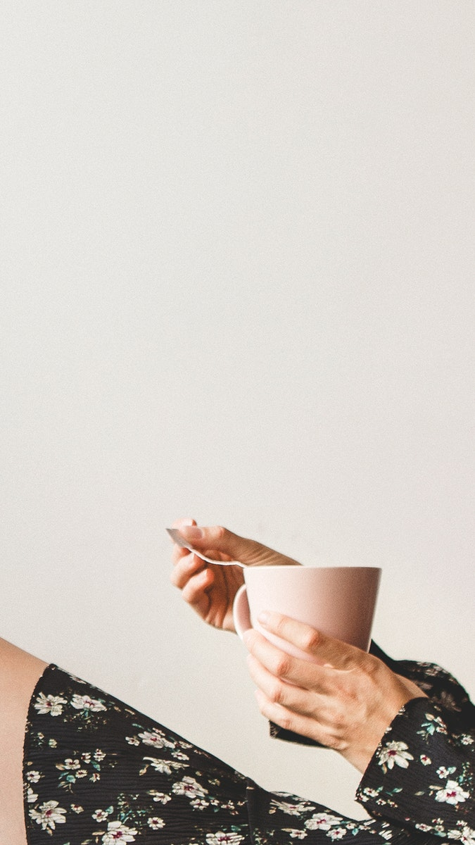 Woman sitting by a white wall with a cup of tea