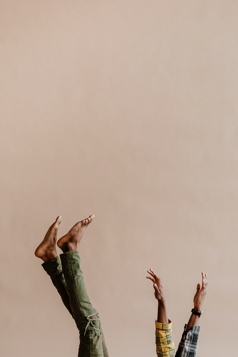 Black man with his feet and hands in the air