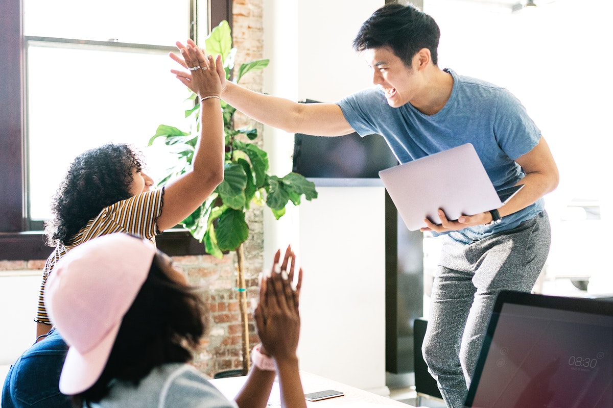 Happy diverse colleagues in a startup company doing a high five