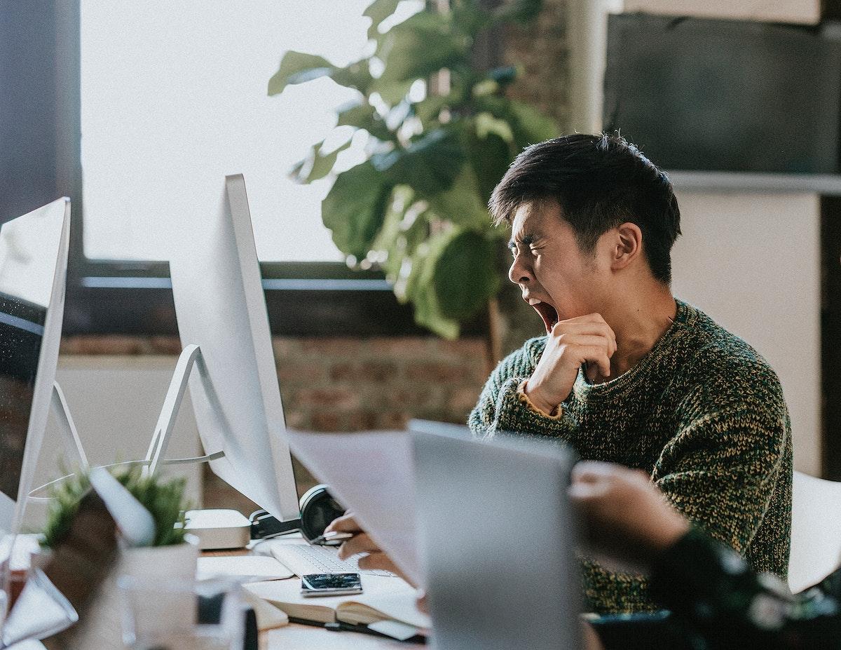 Sleepy businessman yawning in the office