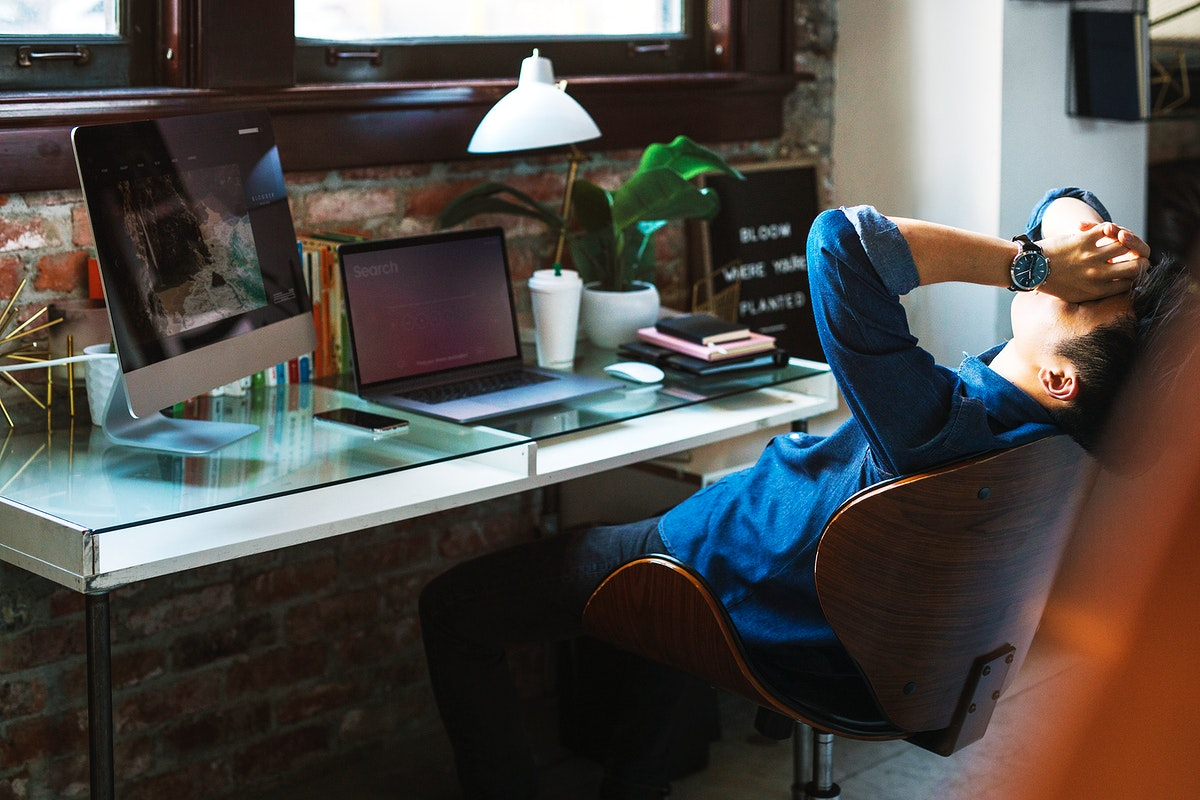 Stressful and exhausted businessman sitting by a computer