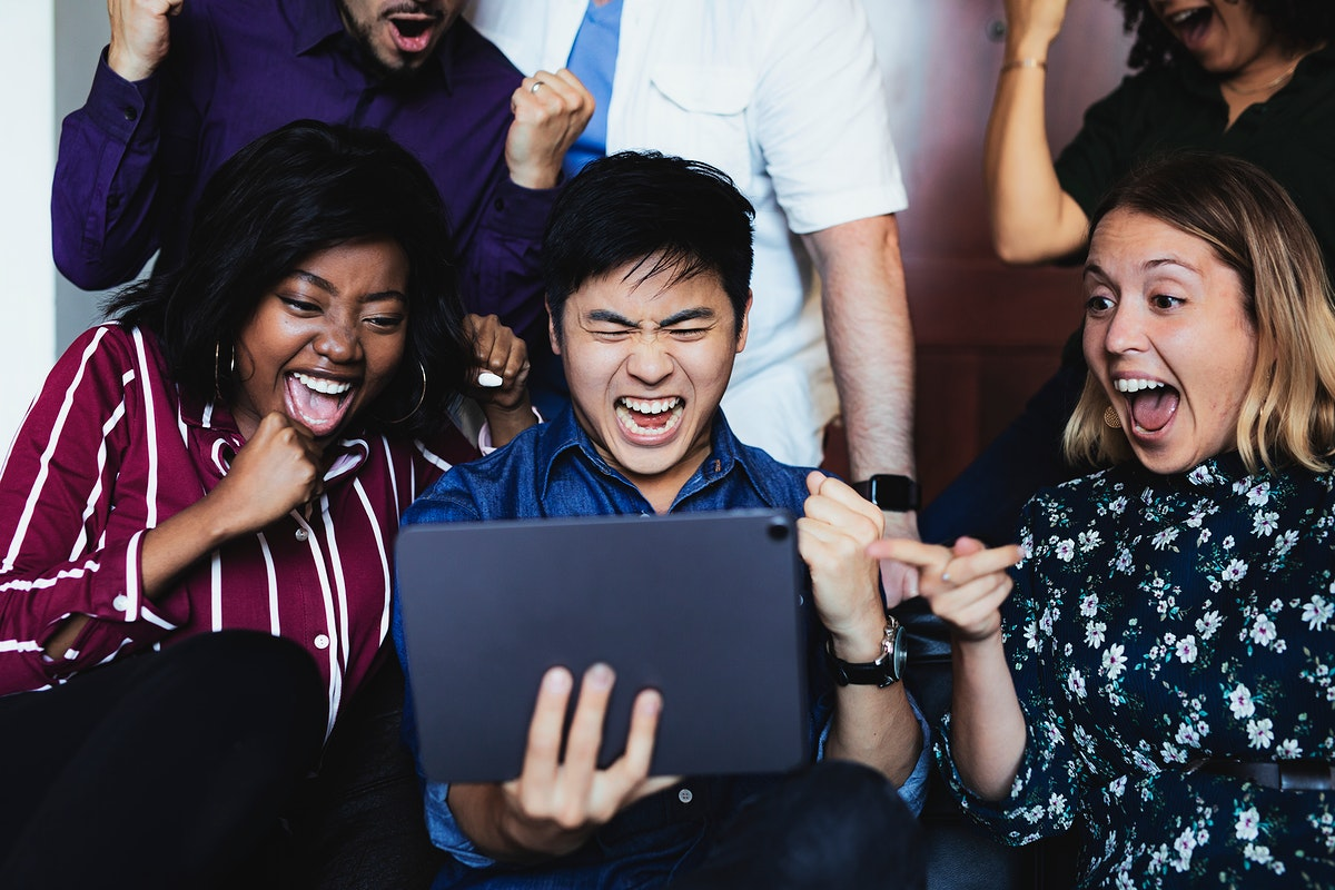 Excited business people looking at a tablet screen