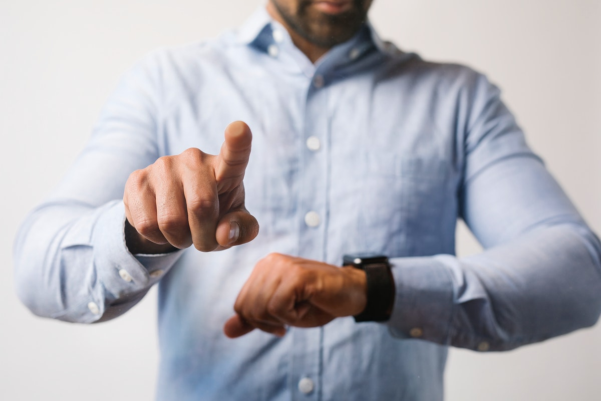 Man in a blue shirt using his smartwatch