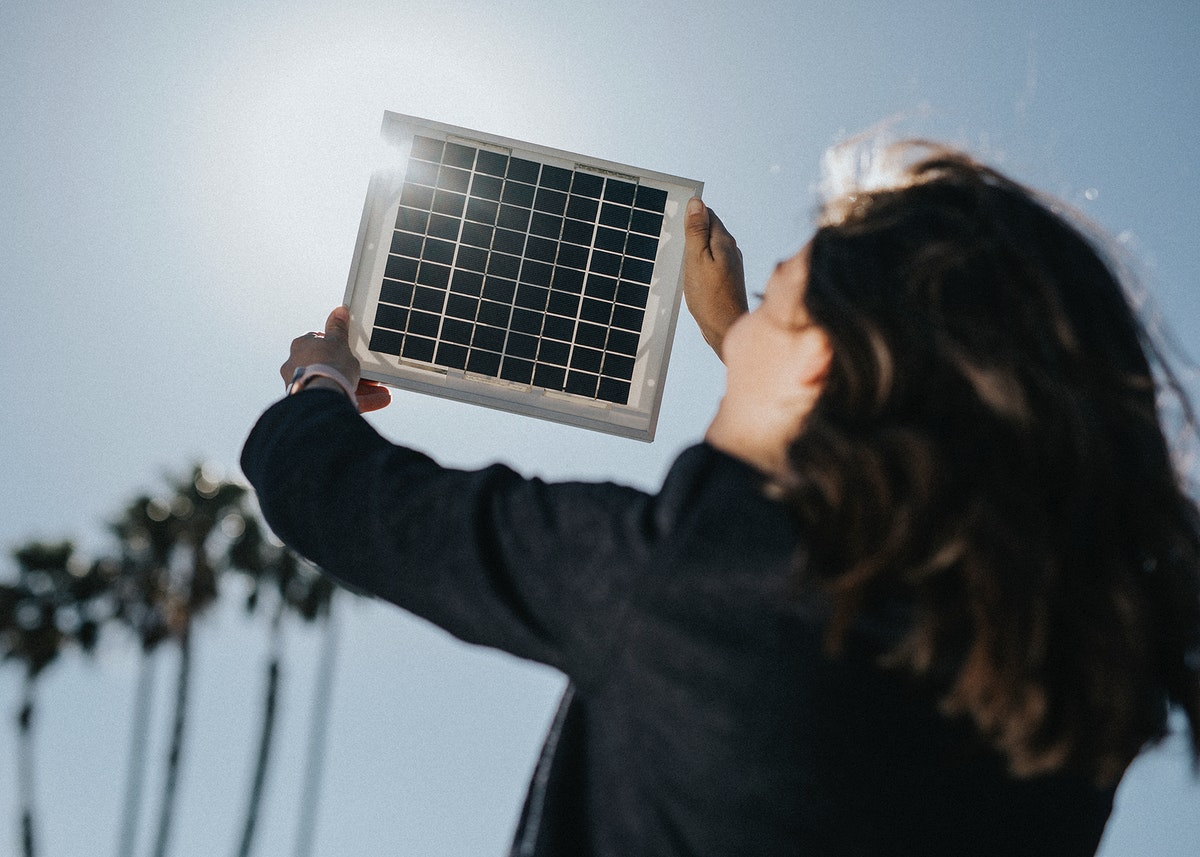 Rearview of eco-friendly woman holding a solar panel up in the sky