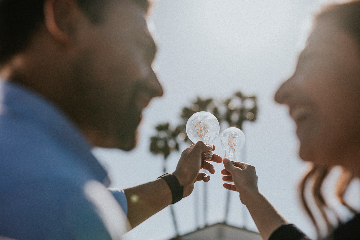 Eco-friendly couple holding the light bulbs up in the sky