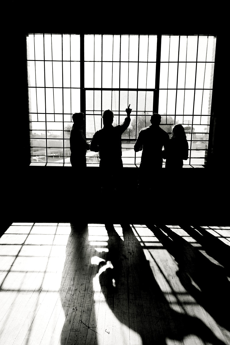Eco-friendly engineering team discussing by the glass windows grayscale