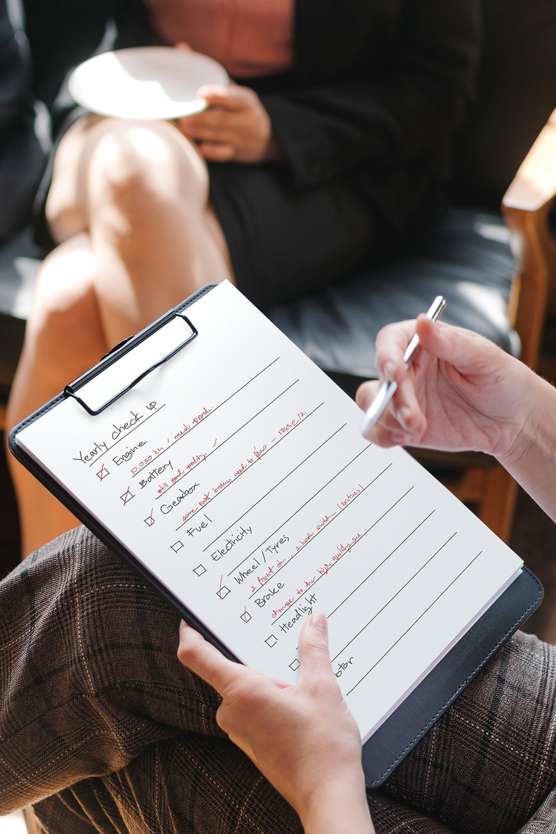 Woman checking a list for automobile checkup