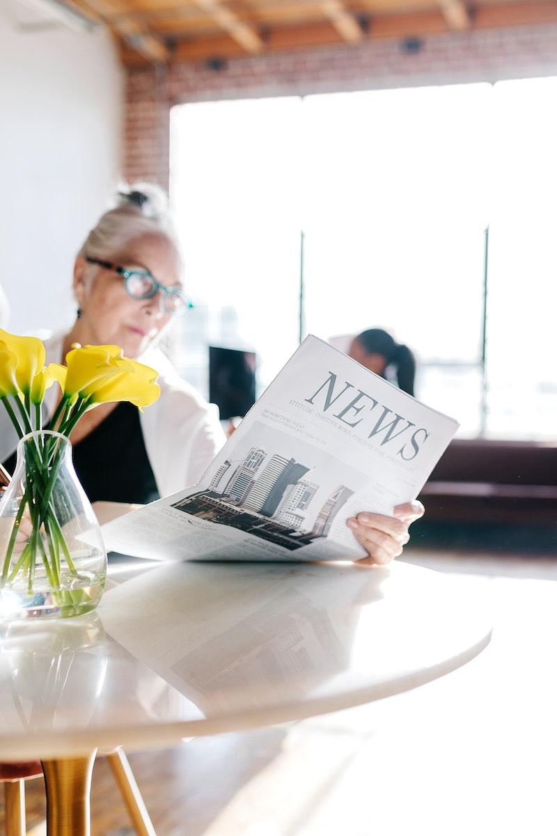 Businesswoman reading newspaper in a workshop