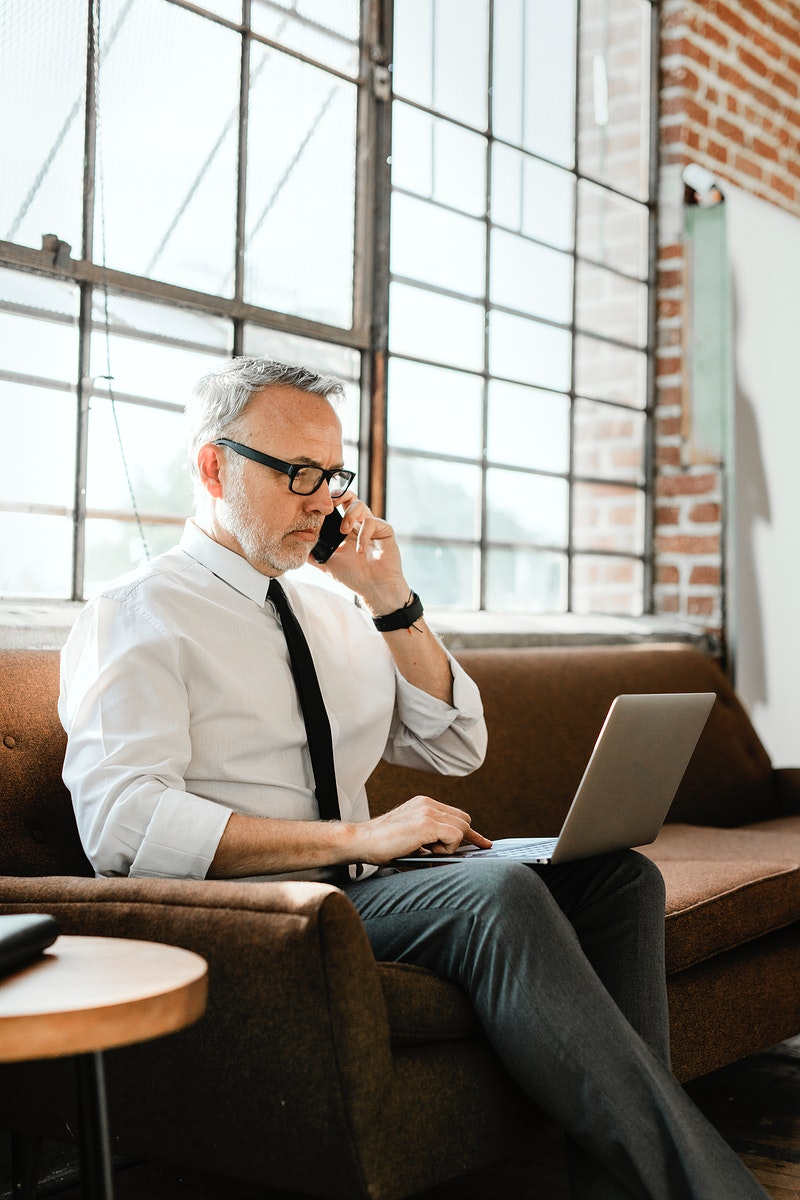 Businessman talking on the phone while using a laptop