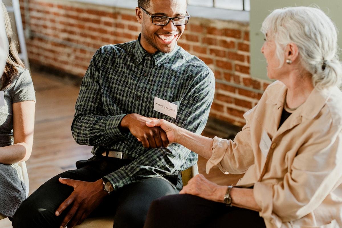 Man handshake with a senior woman