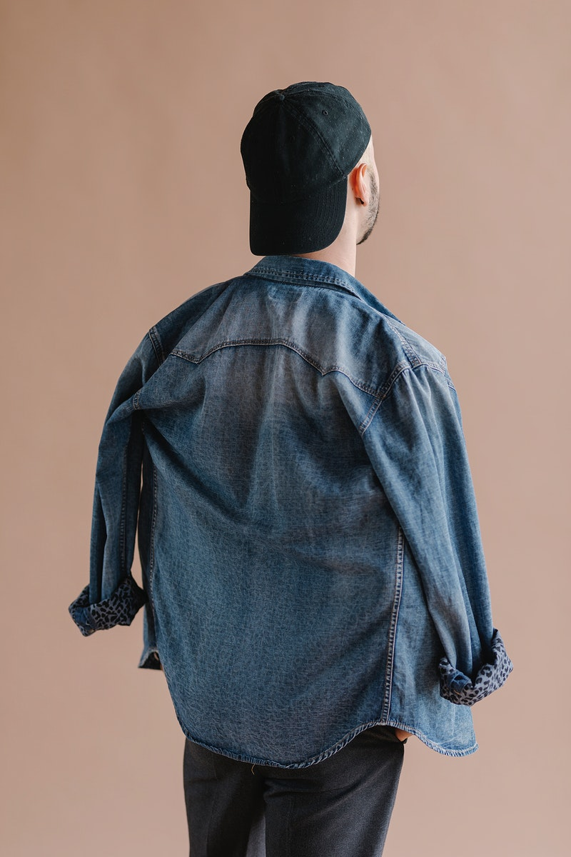 Rearview of a man in a denim jacket with a cap