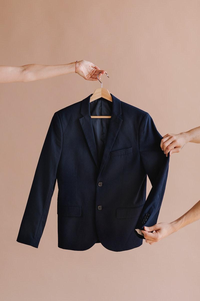 Hands holding a black blazer in a hanger