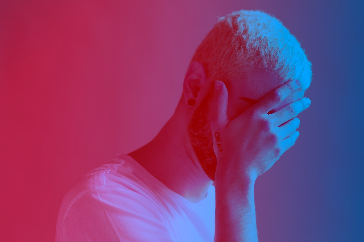 Depressed man covering his face red filter effect