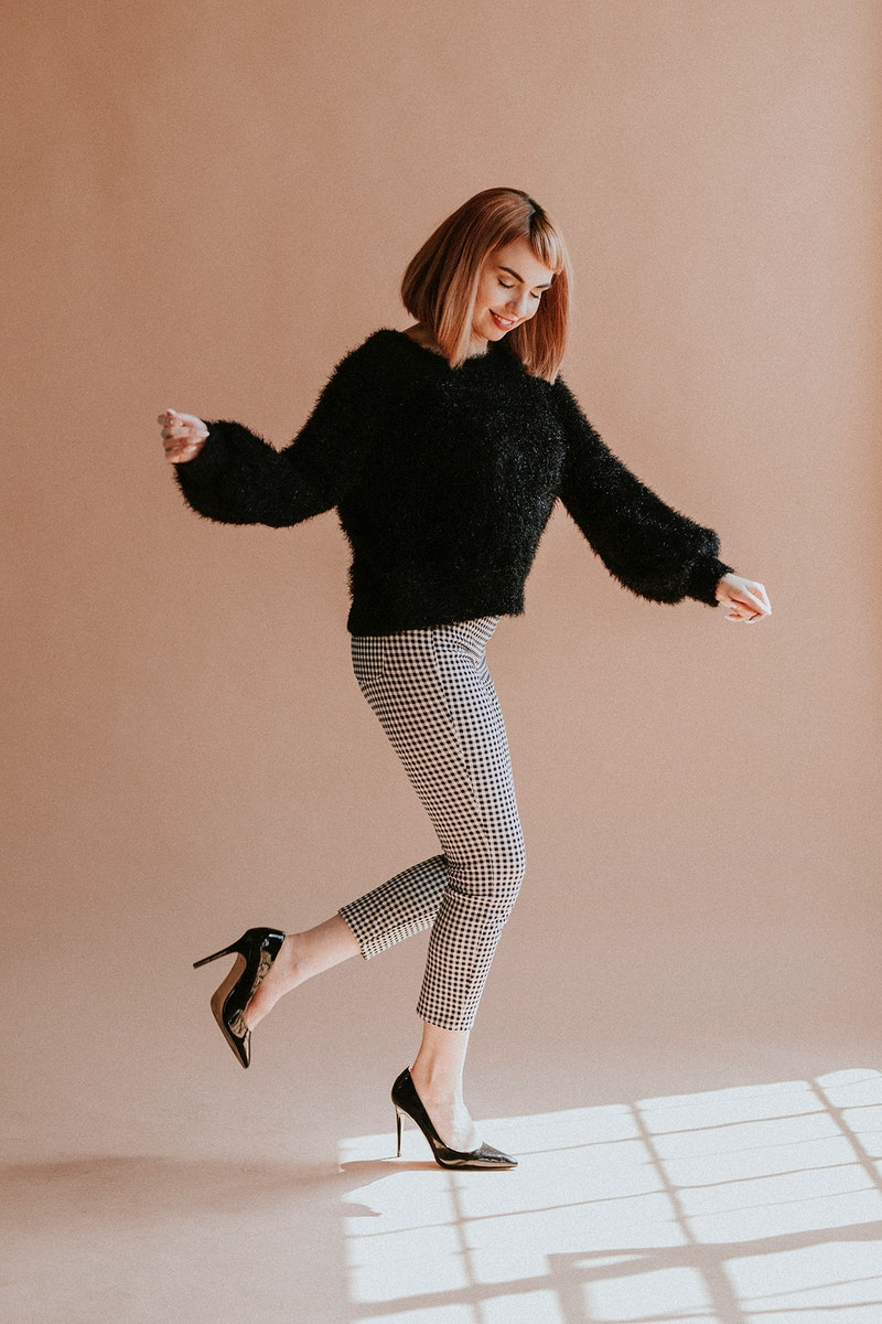 Brown hair woman in a black fluffy sweater hopping with high heels