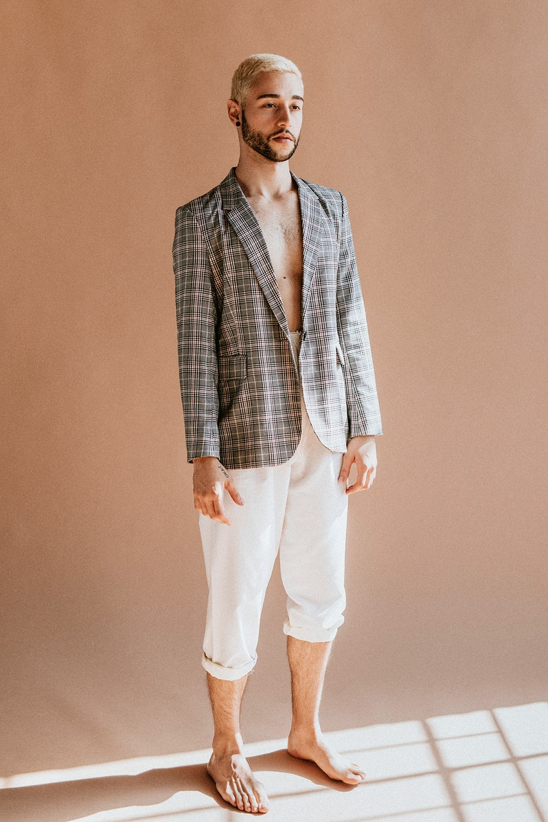 Bearded man in a plaid shirt and white pants