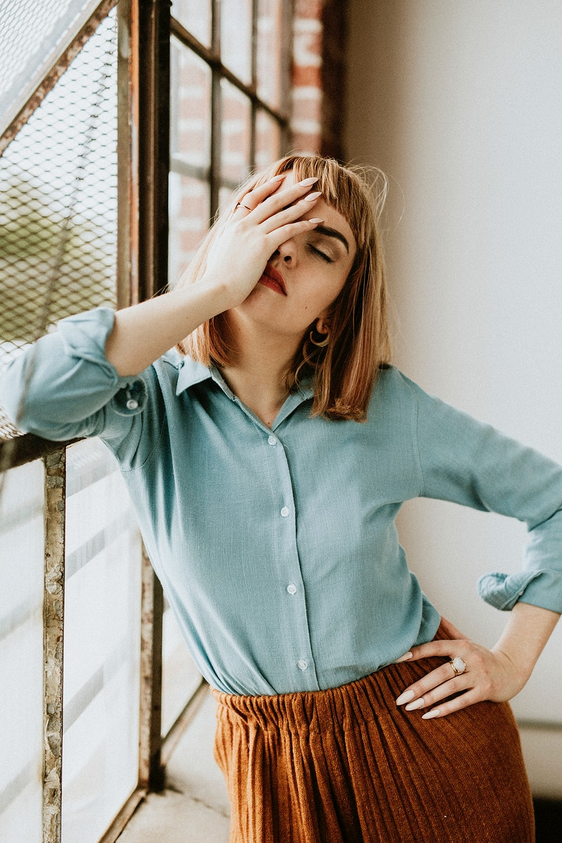 Woman in a blue shirt by the window