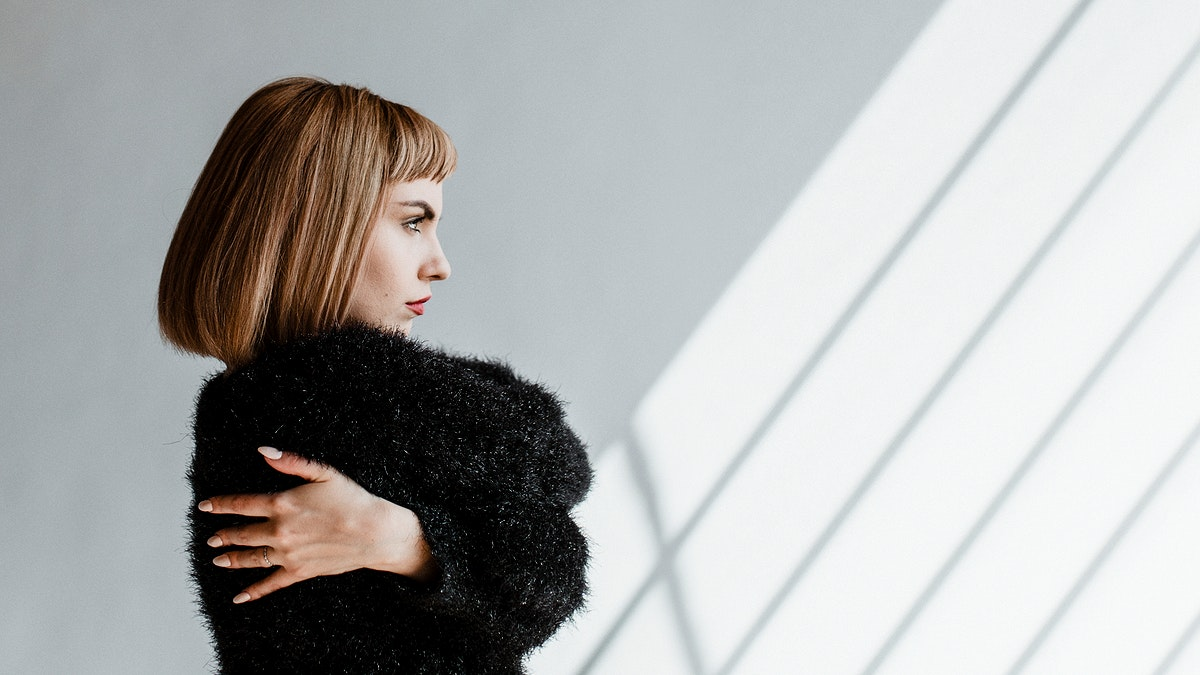Short hair woman in a black fluffy sweater hugging herself