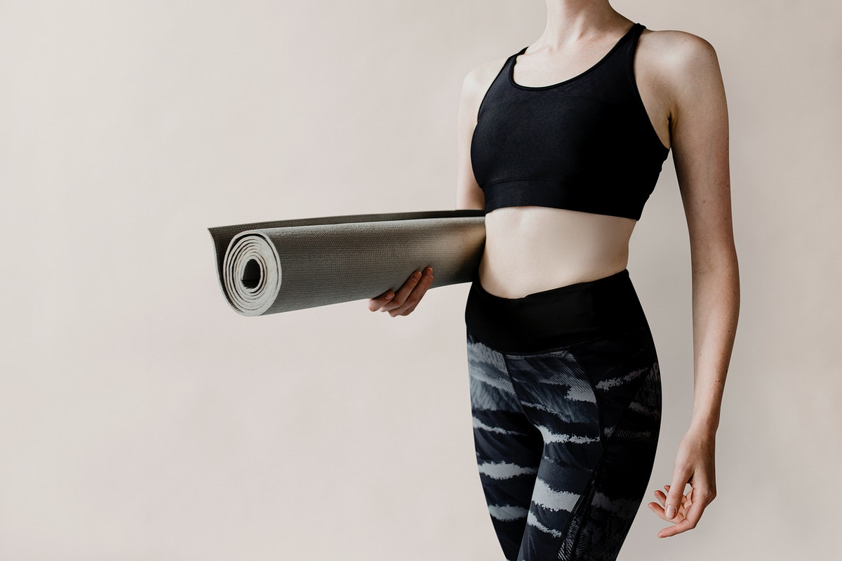 Sportive woman with a yoga mat mockup