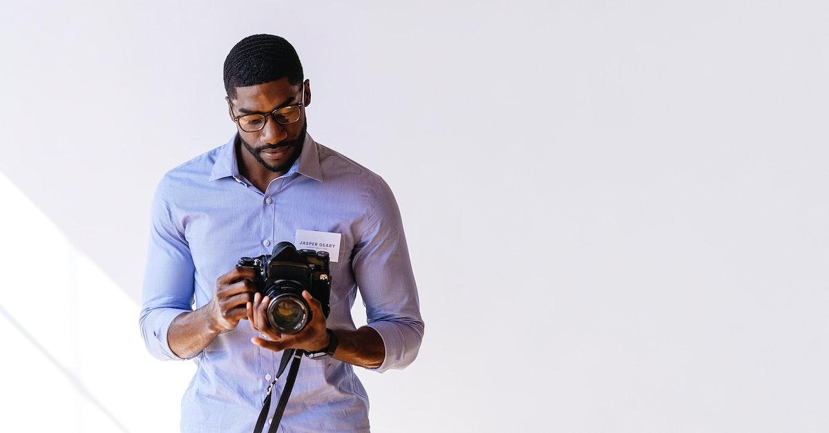 Black photographer using a retro film camera