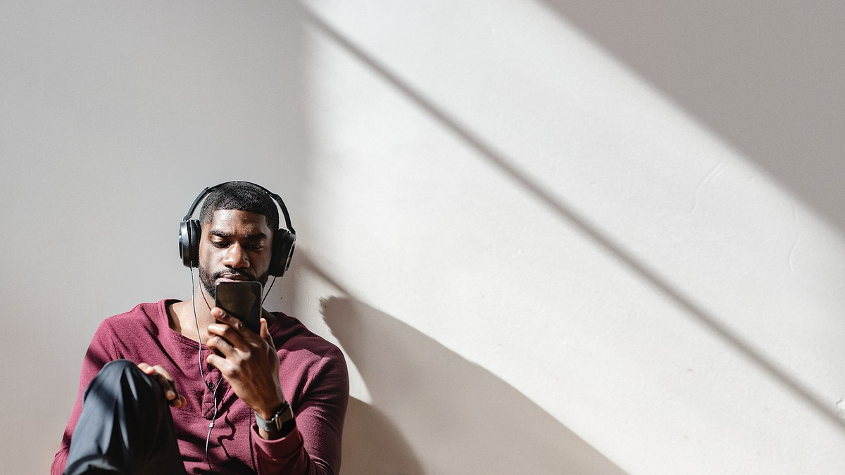 Black man watching a video clip from his phone