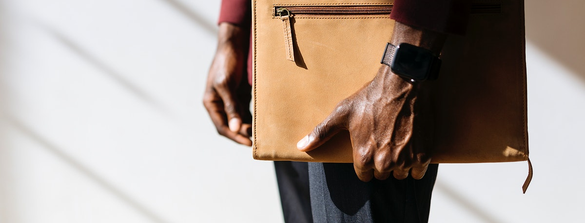 Man with a wristwatch holding a brown briefcase