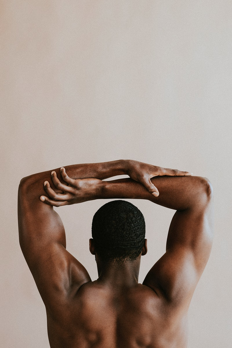 Rear view of black man holding his arms