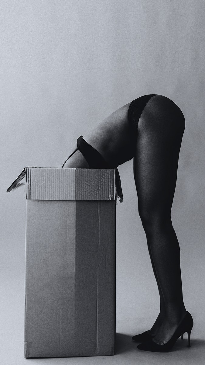 Naked black woman with her head in a cardboard box